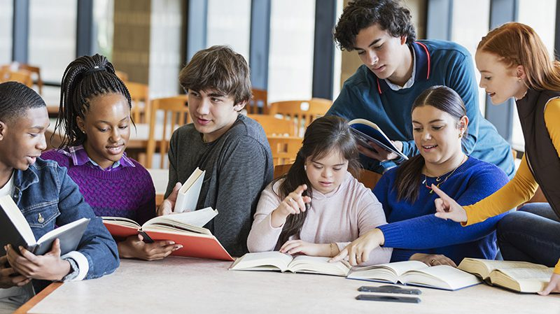 A group of seven multi-ethnic teenagers at a table in the library, reading and studying together. The one sitting in the middle wearing the pink hooded shirt has down syndrome. She is 17 years old mixed race Hispanic and Caucasian. She and her friends, teenage boys and girls, 15 to 17 years old, are smiling, looking down at their books, conversing.